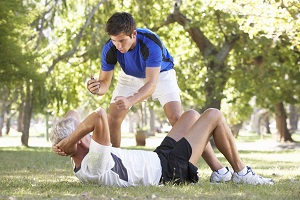 Senior Man Working With Personal Trainer In Park