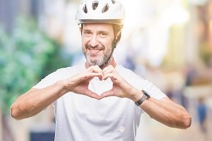 Middle age senior hoary cyclist man wearing bike safety helment isolated background smiling in love showing heart symbol and shape with hands. Romantic concept.